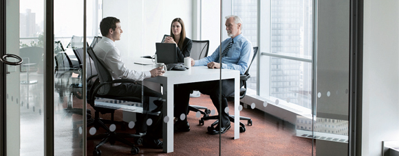 two men and a woman sitting in a meeting room having a meeting.