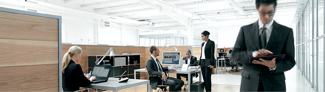 People working in an office and a man walking towards the camera holding a Fujitsu M532 tablet