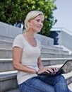 Photo of a woman sitting on steps with a laptop