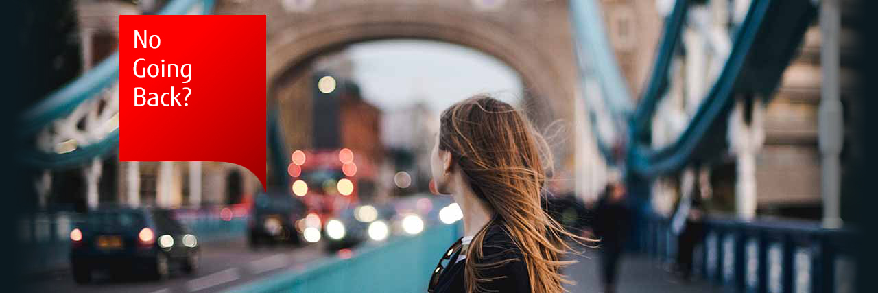 Photo of a woman looking back over Tower Bridge in London