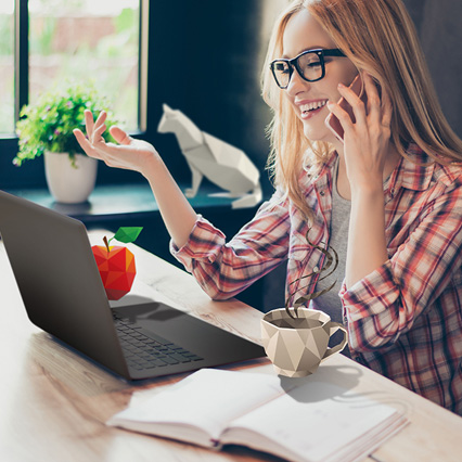 woman talking on phone using laptop next to origami apple and coffee